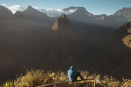 Rear view of man looking at mountains while sitting on observation point - CAVF59177