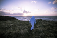 Denmark, Nordjuetland, Man wearing ice bear costume at the beach - REAF00468
