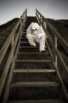 Man wearing ice bear costume sitting on steps, despair - REAF00474