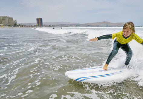Chile, Arica, happy boy surfing in the sea - SSCF00076