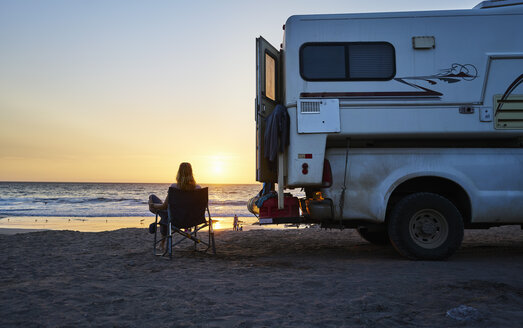 Chile, Arica, woman sitting next to camper on the beach at sunset - SSCF00079