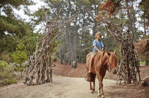Boy riding on horse through a forest - SSCF00091