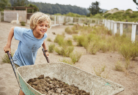 Smiling boy pushing wheelbarrow with horse dung - SSCF00097