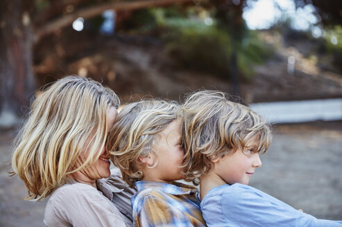 Happy mother with two sons sitting in a row outdoors - SSCF00100