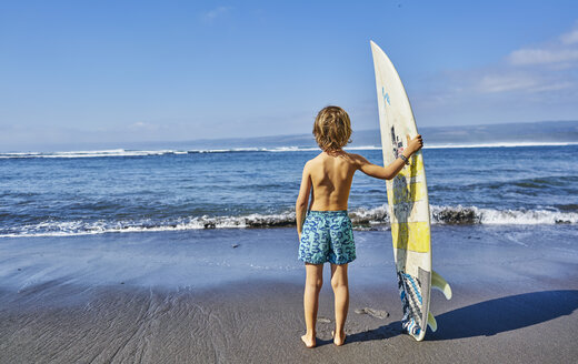 Chile, Pichilemu, boy standing at the sea with surfboard - SSCF00121