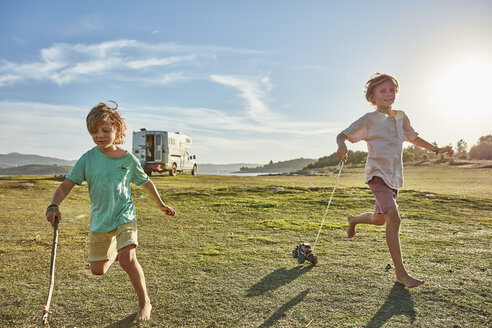 Chile, Talca, Rio Maule, two boys running on meadow with toy cars beside camper - SSCF00124