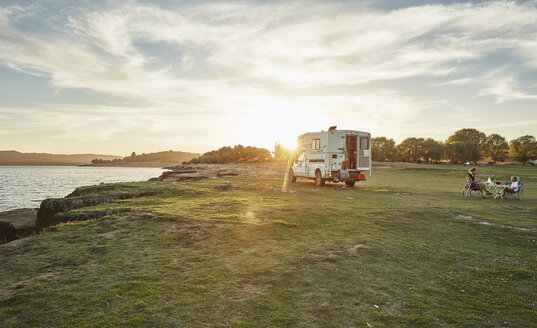 Chile, Talca, Rio Maule, camper at lake with family having dinner at sunset - SSCF00127