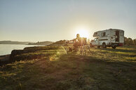 Chile, Talca, Rio Maule, camper at lake with woman and dog at sunset - SSCF00130