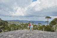 Chile, Puren, Nahuelbuta National Park, woman standing with sons on boulder looking at Araucaria forest - SSCF00151