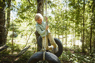 Happy boy balancing on tyres at an adventure park in forest - SSCF00157