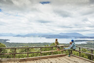 Chile, Puren, Nahuelbuta National Park, woman with two sons sitting on observation terrace overlooking the lake - SSCF00160