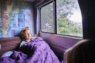 Boy in pyjama looking out of window of a camper - SSCF00163