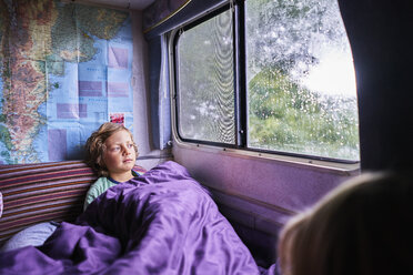 Boy in pyjama looking out of window of a camper - SSCF00163