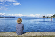Chile, Puerto Montt, boy sitting on quay wall at the harbor - SSCF00181