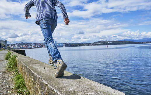 Chile, Puerto Montt, boy running on quay wall at the harbor - SSCF00184