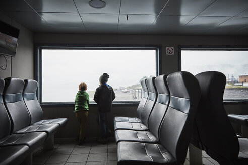 Chile, Puerto Montt, two boys looking out of window of a ferry - SSCF00187