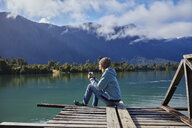 Chile, Chaiten, Lago Rosselot, woman sitting on jetty holding mug - SSCF00214