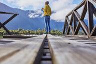 Chile, Chaiten, Lago Rosselot, woman standing on jetty holding mug - SSCF00217