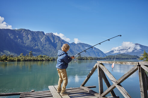 Chile, Chaiten, Lago Rosselot, boy standing on jetty fishing in lake - SSCF00220