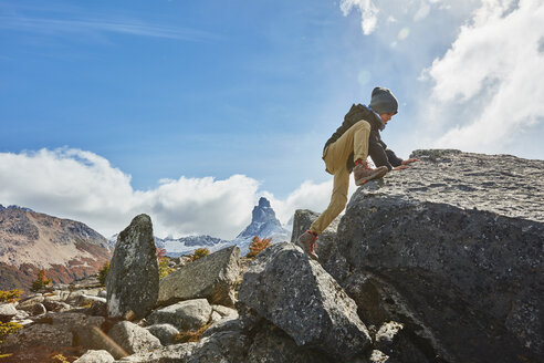 Chile, Cerro Castillo, boy climbing on rock in mountainscape - SSCF00235