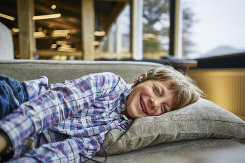 Happy boy lying on couch with earphones - SSCF00256