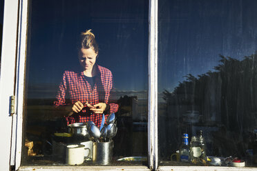 Woman behind kitchen window preparing meal - SSCF00262