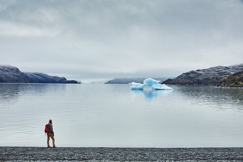 Chile, Torres del Paine National park, Lago Grey, woman standing at the shore looking at iceberg - SSCF00277