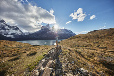 Chile, Torres del Paine National park, woman standing on rock in front of Torres del Paine massif at sunrise - SSCF00286