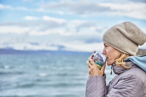 Chile, Torres del Paine National Park, woman drinking from mug at Lago Paine - SSCF00292