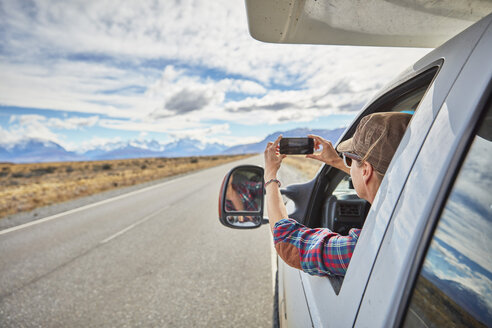 Argentina, Patagonia, El Chalten, woman taking cell phone picture in camper on road towards Fitz Roy - SSCF00301