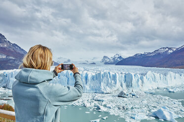 Argentina, Patagonia, Perito Moreno glacier, woman taking cell phone picture of glacier - SSCF00328