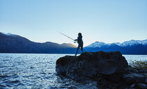 Argentina, Patagonia, Lago Futalaufquen, boy fishing in lake at dusk - SSCF00331