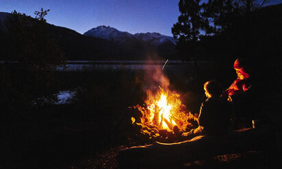 Argentina, Patagonia, Lago Futalaufquen, mother with sons at camp fire at night - SSCF00334