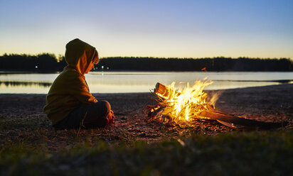 Argentina, Patagonia, Concordia, boy sitting at camp fire at a lake - SSCF00340