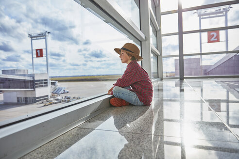Boy sitting behind windowpane at the airport looking at airfield - SSCF00343