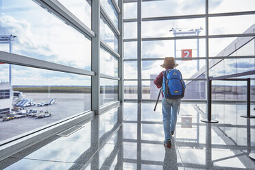 Boy with backpack at the airport running towards departure gate - SSCF00346