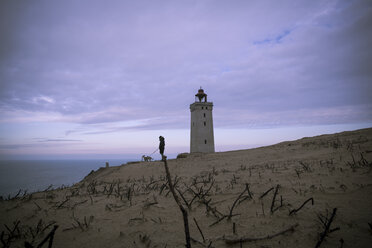 Denmark, North Jutland, man with dog looking at view near Rubjerg Knude Lighthouse - REAF00483