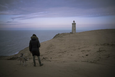 Denmark, North Jutland, back view of man with dog looking at Rubjerg Knude Lighthouse at blue hour - REAF00489