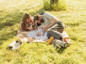 Young couple relaxing with baby girl on blankets on a meadow - LAF02188