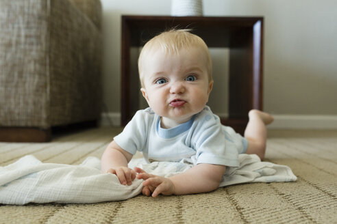 Portrait of cute playful baby boy making face while lying on carpet at home - CAVF59210