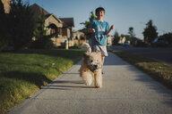 Boy with dog on footpath amidst field - CAVF59225