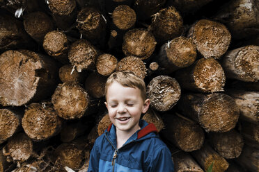 Smiling boy with eyes closed standing by logs - CAVF59267