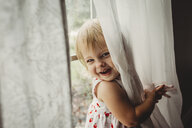 Portrait of cheerful girl playing with curtains by window at home - CAVF59303