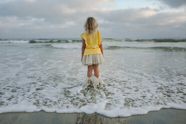 Rear view of girl standing in sea at beach - CAVF59309