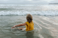 Carefree girl sitting in sea at beach - CAVF59315