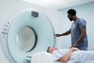 Male nurse adjusting button on MRI Scanner while patient lying in examination room - CAVF59378