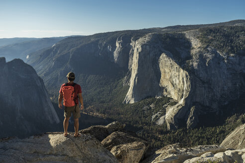Rear view of male hiker standing on cliff at Yosemite National Park - CAVF59387