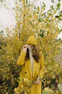 Woman covering face while standing against plants during autumn - CAVF59393