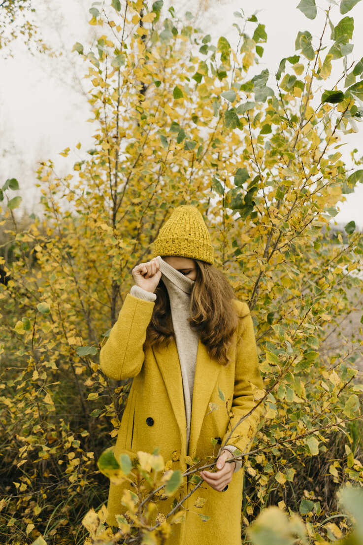 Woman covering face while standing against plants during autumn - CAVF59393 - Cavan Images/Westend61