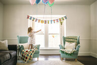 Girl decorating balloons in living room for birthday party - CAVF59399